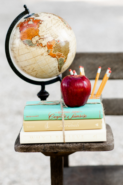 A globe, red apple, jar of yellow pencils, and books tied with twine sitting on a wooden desk ready to homeschool.