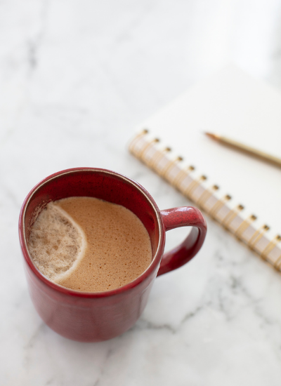 A red mug with coffee sitting next to a notebook and pen on a marble countertop.