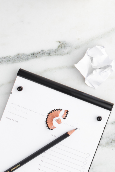 A list pad of paper sitting on a marble countertop with a lack pencil and pencil shavings on top.