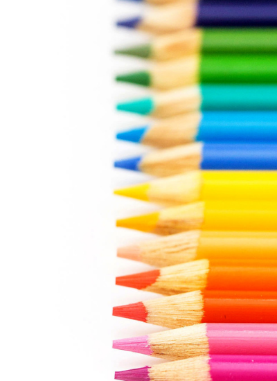 A line of colored pencils lined up in a rainbow.