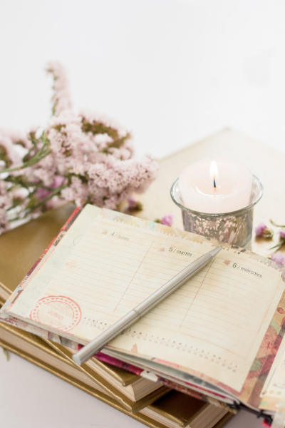 An open, distressed journal with a pen on top sitting next to a lit candle and a bunch of flowers.
