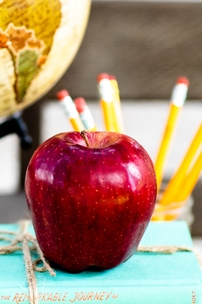 A close up view of a red delicious apple sitting in front of some yellow pencils and on top of a book.