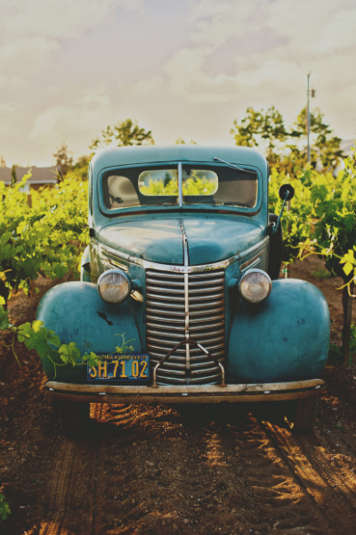 An old, beat-up blue pickup truck sitting in a field, ready to help.