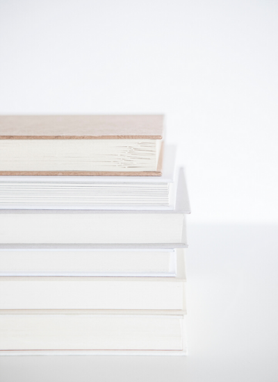 A stack of books sitting on a white table.