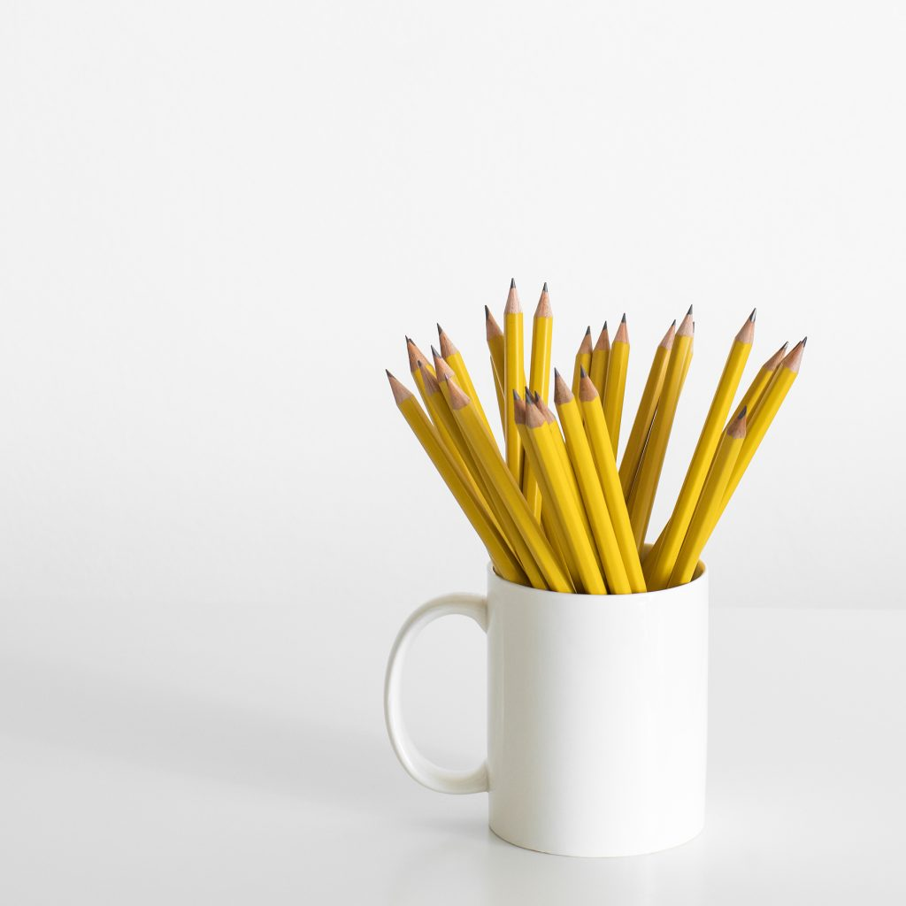 A white mug filled with yellow sharpened pencils ready for the homeschool day.