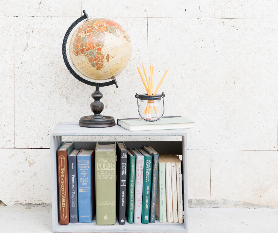 A globe and a jar of yellow pencils sitting on a wooden crate filled with all sorts of books.