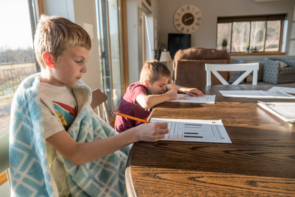 Two young boys sitting at a kitchen table and working on their school work, showing that you cannot measure one child's progress by their sibling's.