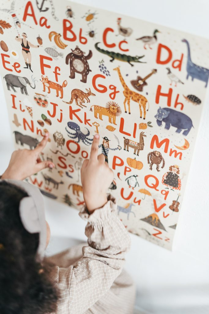 A young girl studying an ABC chart and matching the letter to the picture that starts with that sound.