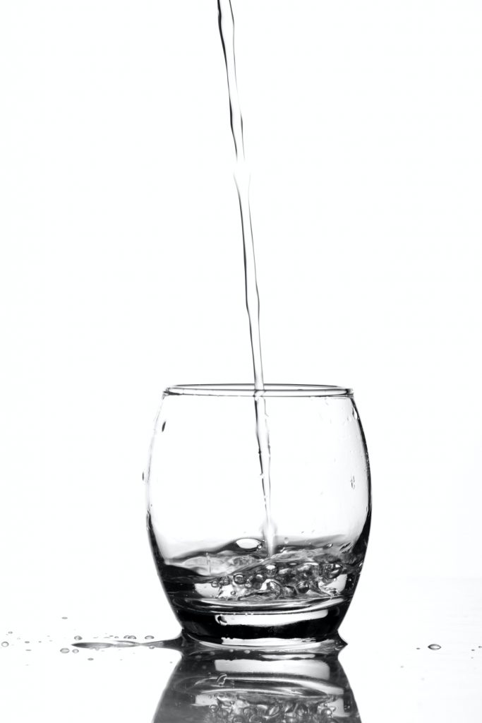 Water pouring from a height into a clear glass.