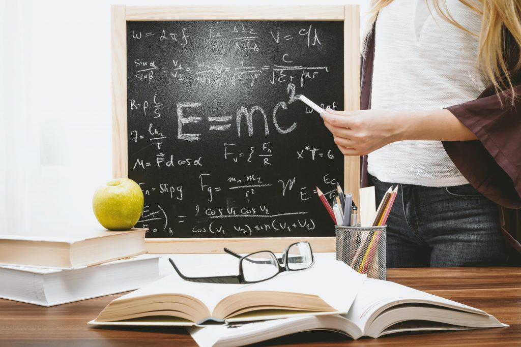 A high school aged girl standing next to a chalkboard filled with equations. On the table in front of her are piles of school books and an apple.