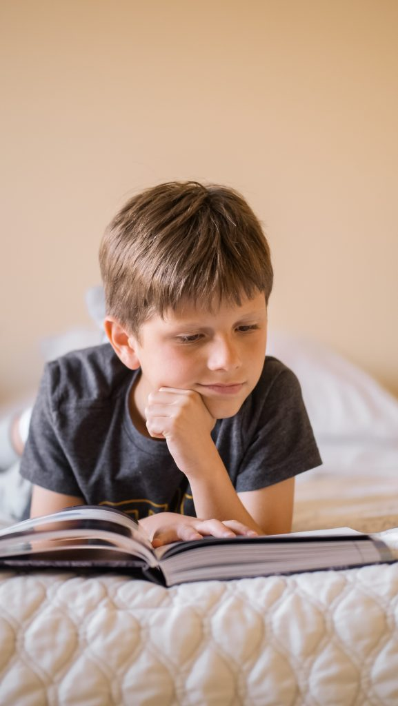 A young boy laying on his stomach and reading a book, perhaps James and the Giant Peach by Roald Dahl.