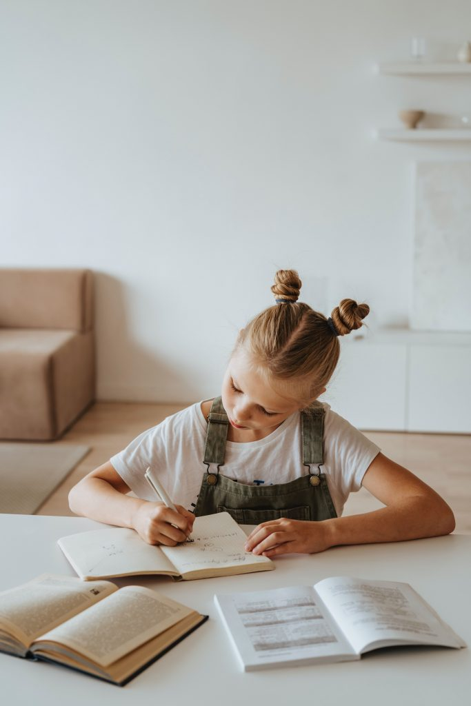 A young girl sitting at a table, working on her homeschool work with books all around her.