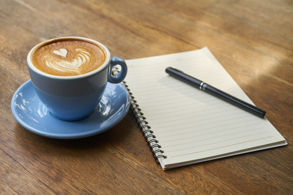 A cup of coffee in a blue mug, sitting on a saucer next to a spiral bound notebook with a pen sitting on top, ready for the day's list.