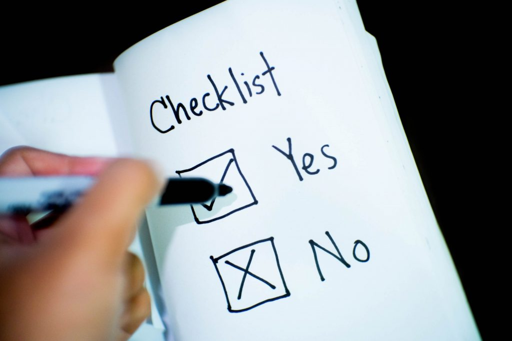 An open notebook with the word 'checklist' and underneath it the words 'yes' and 'no' while a person holds a pen over the answers.