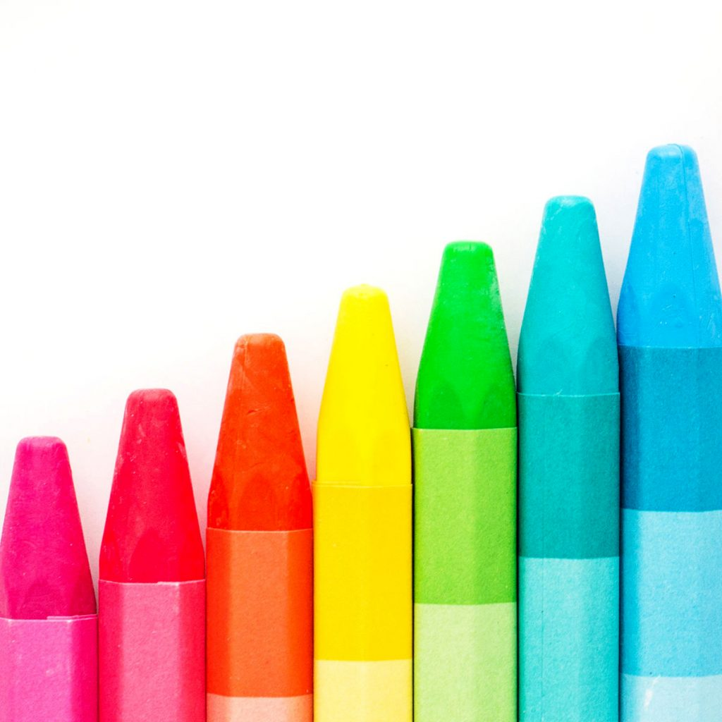 Brightly colored crayons lined up in a stair step formation like you would use in the early years of homeschooling.