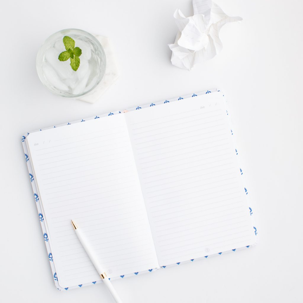 A pen sitting on top of a lined notebook next to a glass of water, ready for some homeschool learning.