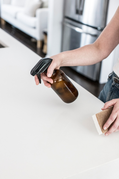 A person in a white tee-shirt holding a spray bottle and a sponge getting ready to do the chore of cleaning the counter.