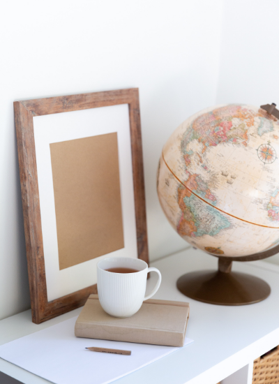 A notebook, pencil, and cup of coffee sitting next to a globe of the world.