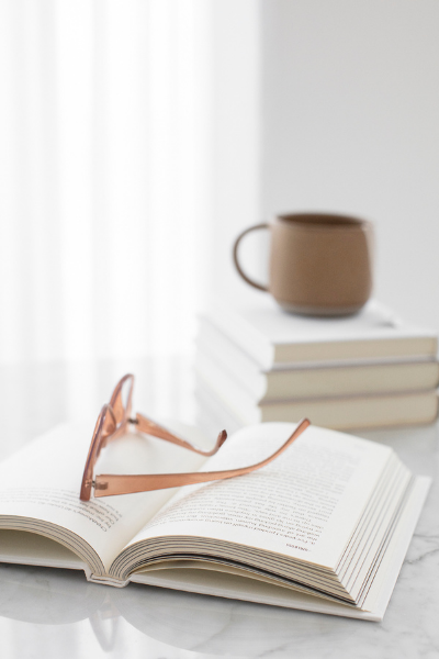 A cup of coffee sitting on a stack of books while a pair of reading glasses sits on an open book in the foreground.