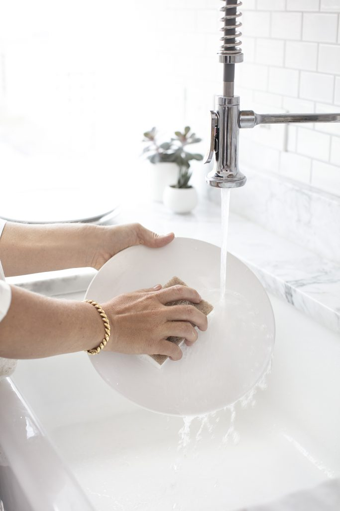 The hands of a person washing a white dish under running water showing why chores are important.