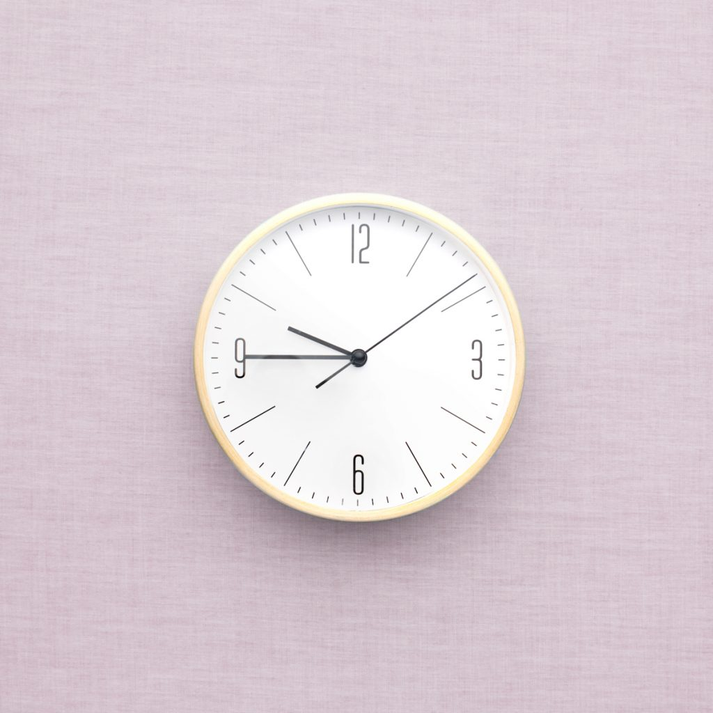 A white analog clock on a pink wall.