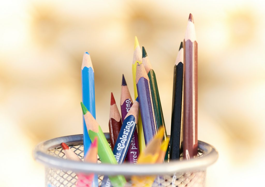 A wire mesh pencil holder holding colored pencils for homeschooling.