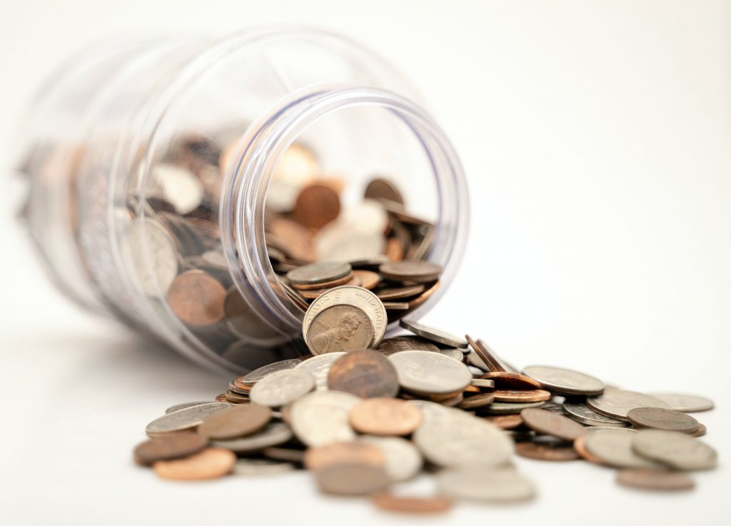 Coins spilling out of a mason jar on its side showing that you can get paid for doing chores in your house.