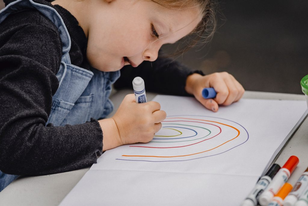 A picture of a young girl drawing a rainbow with markers.