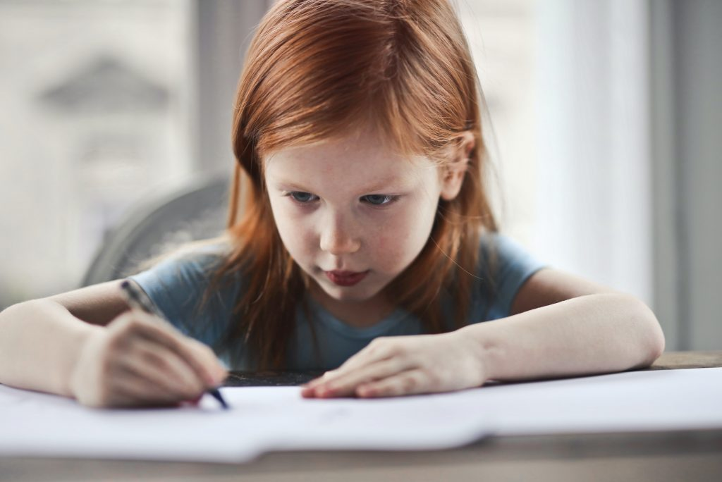 A young girl working on her homeschool lessons at a table.