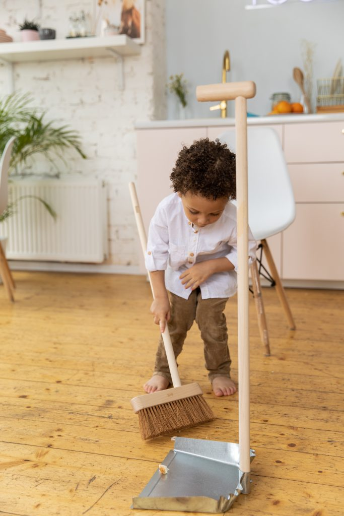 A young boy working on his chore of sweeping the floor with a broom his size.
