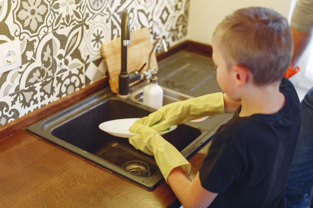 A young boy standing at the kitchen sink and washing dishes, showing that you're never too young to help with chores in your house.