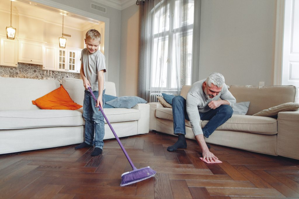 A young boy and his grandpa working together to accomplish the chore of sweeping the floor.