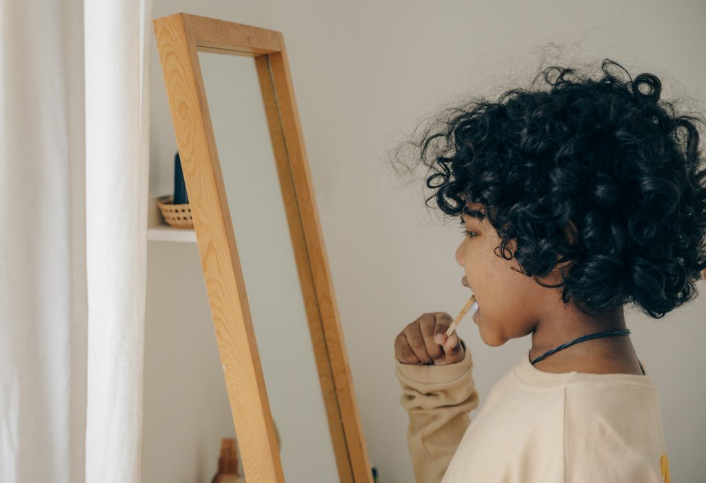 A young girl standing in front of a mirror brushing her teeth.