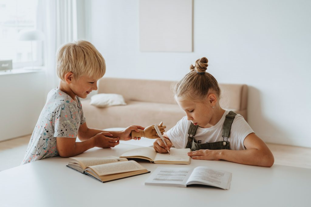 A brother and sister sitting at a table working on their homeschooling work with books in front of them.