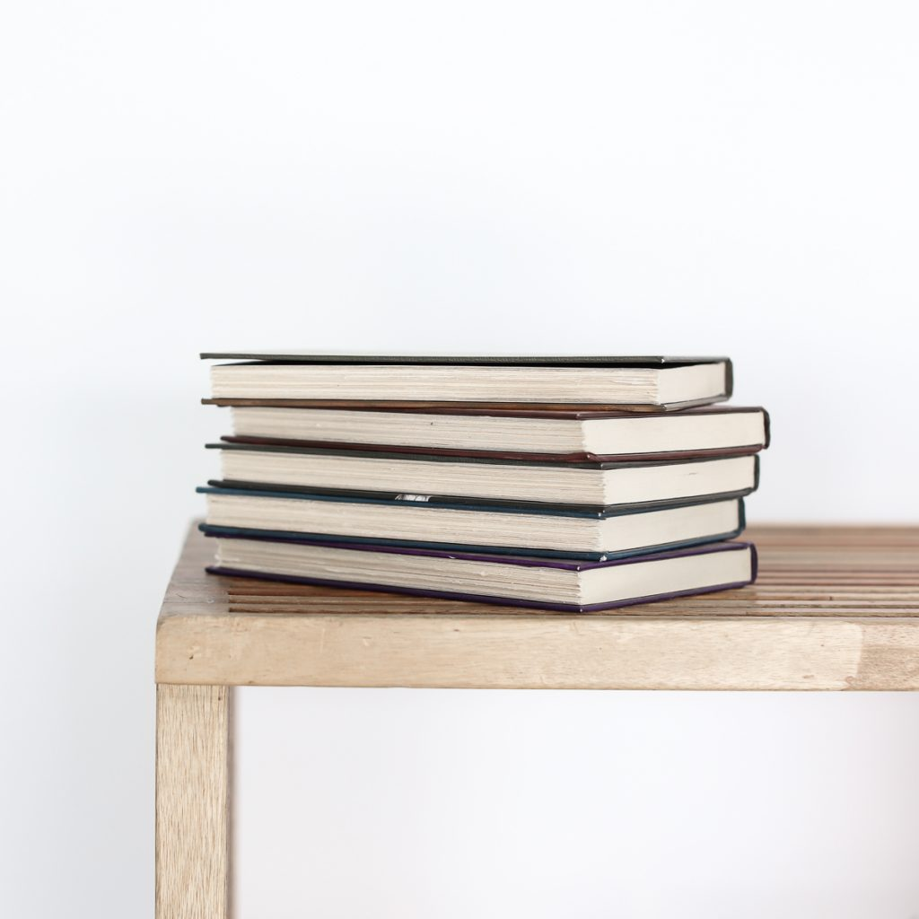 A stack of hardcover chapter books sitting on a wooden table against a white background.