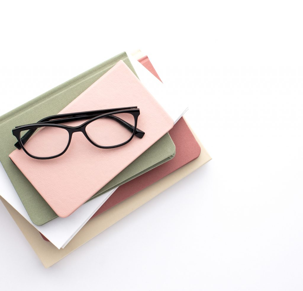 A colorful stack of books like you might use to teach your child to read with a pair of glasses sitting on top.