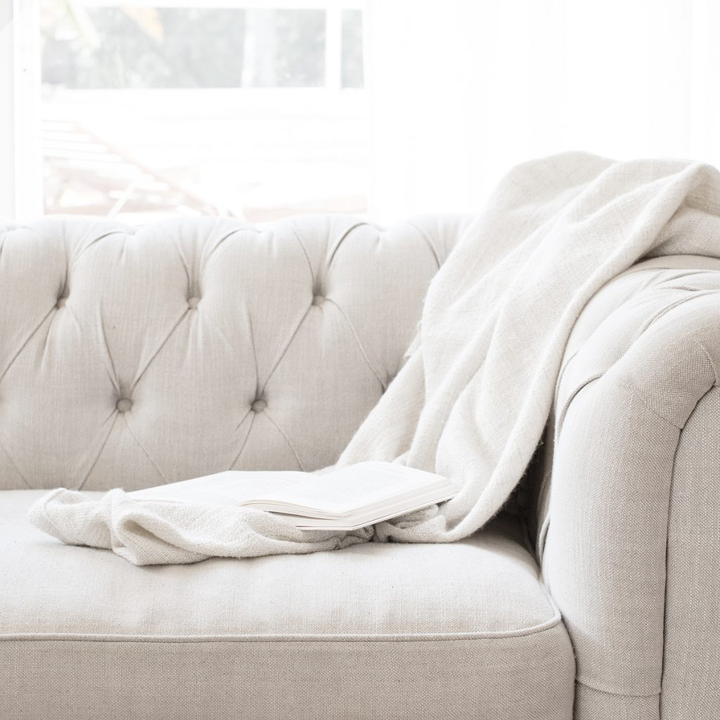 A cream colored couch with an open book laying on it just waiting to be read.