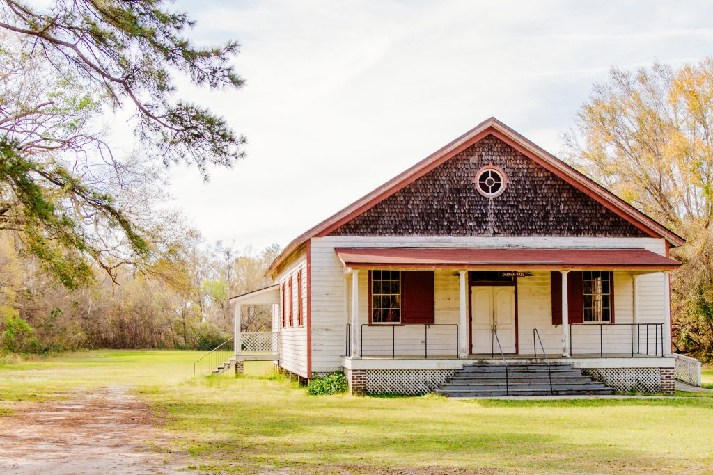 A one room schoolhouse sitting in a green field.