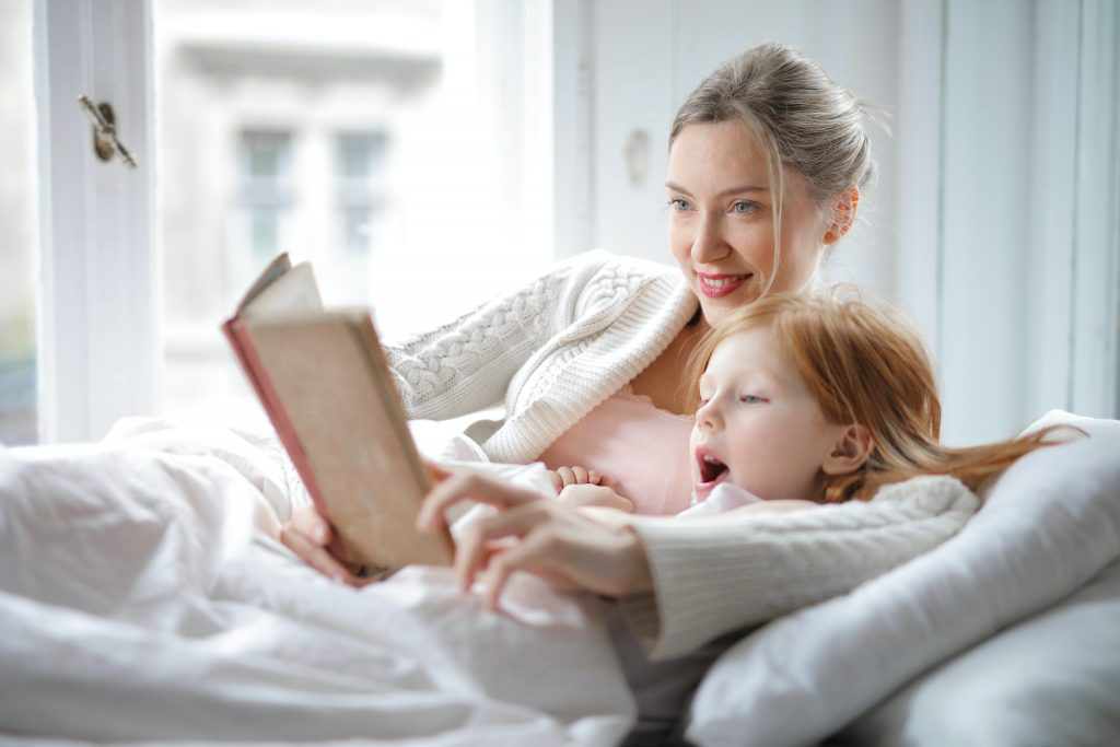 A mom snuggling with her daughter as the daughter sounds out words, learning how to read.