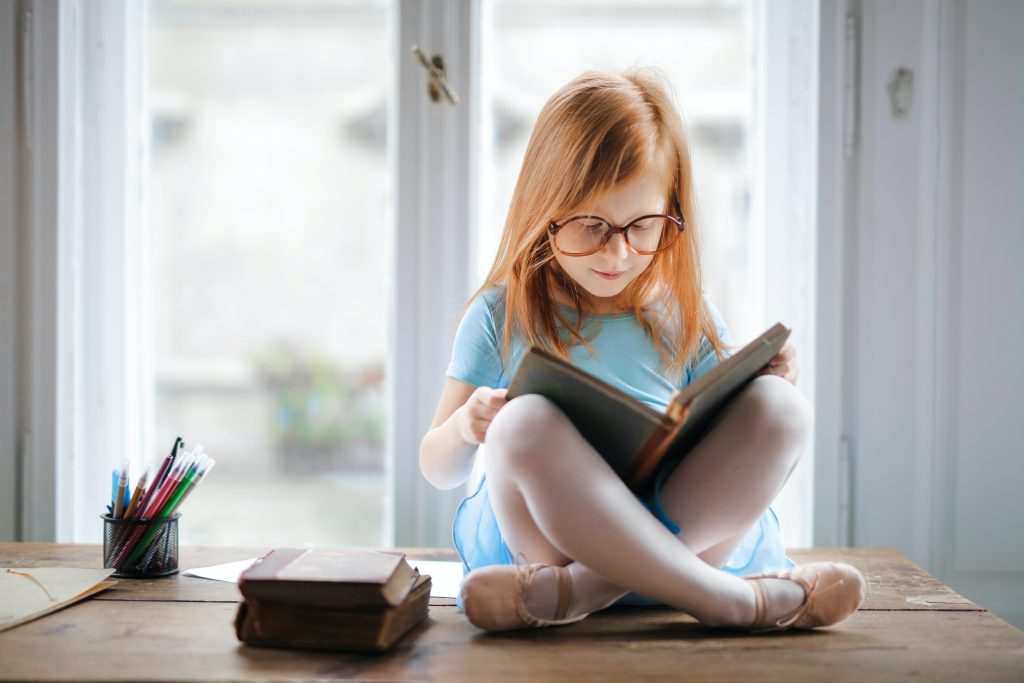 A young, red-headed girl wearing glasses sitting cross-legged in front of a window reading a book.