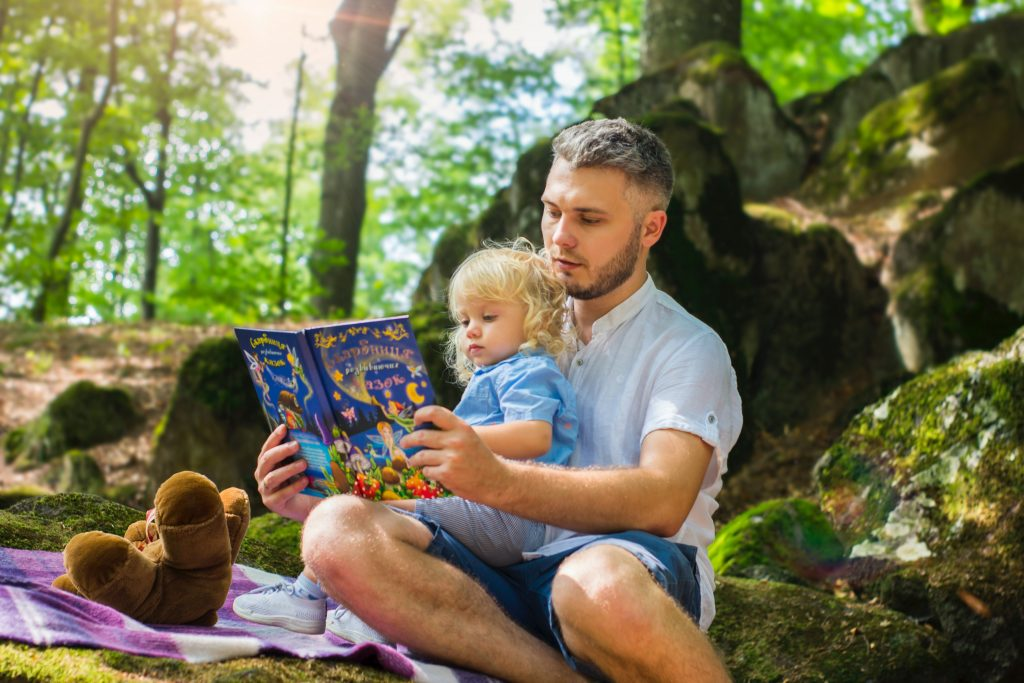 A father sitting outside reading a book to his young daughter.