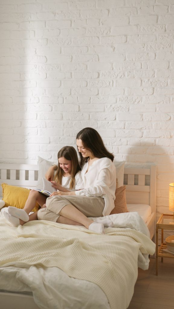 A mom and a daughter snuggling together as the daughter reads a book to her mom.