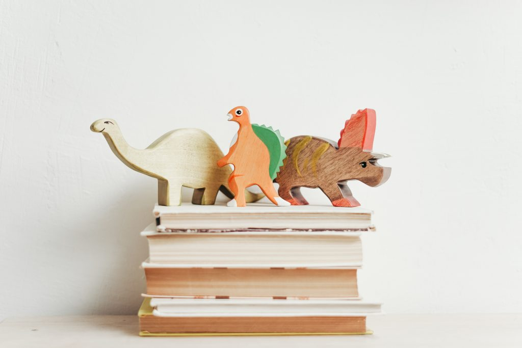 A stack of young children's books with wooden dinosaurs standing on top.