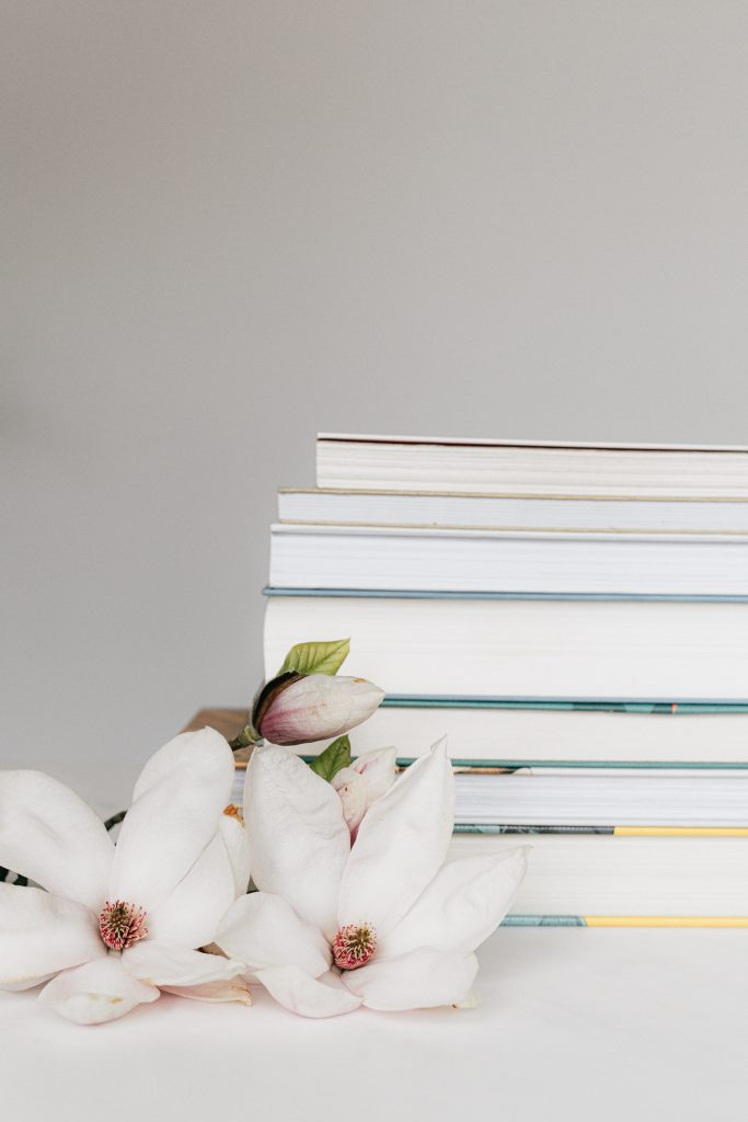 A stack of books showing the pages with some white flowers laying next to them on the table.