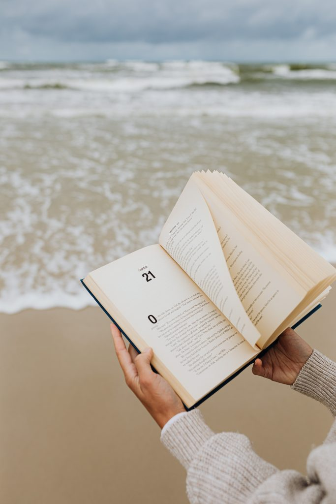A lady holding a chapter book open on the beach as you see the waves crashing on the shore in the background.