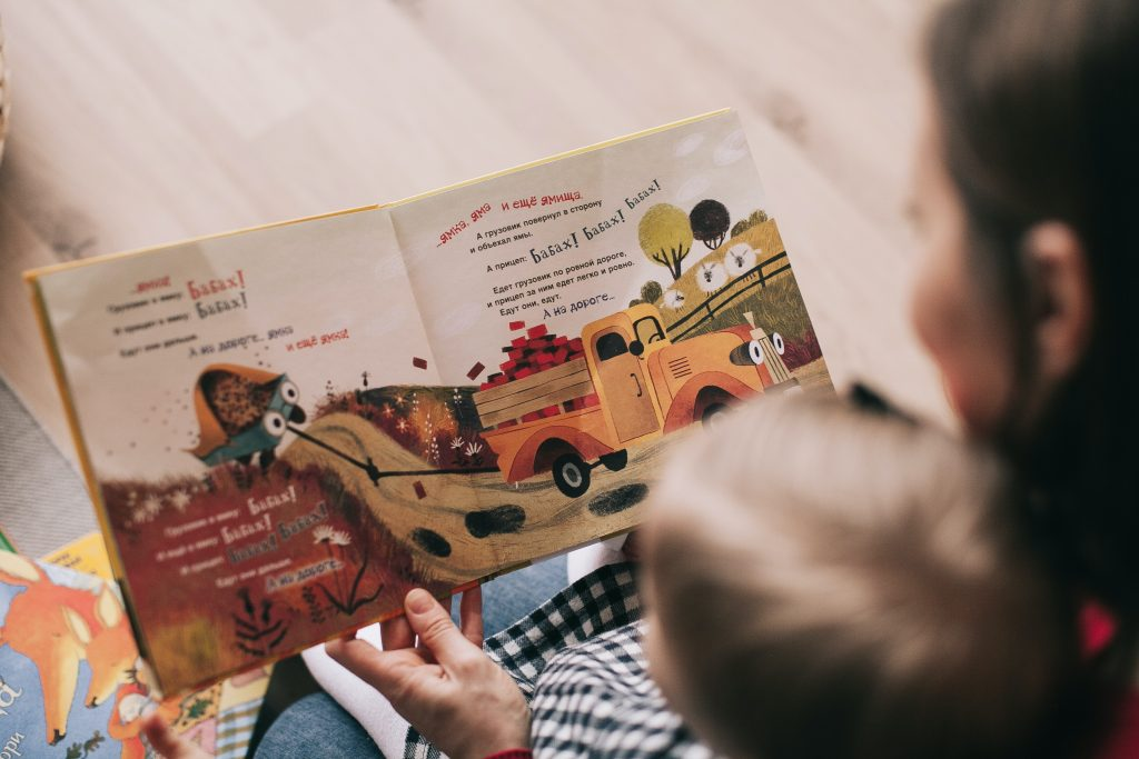 Looking over a mother's shoulder as she reads 'A Little Blue' truck to her young son.