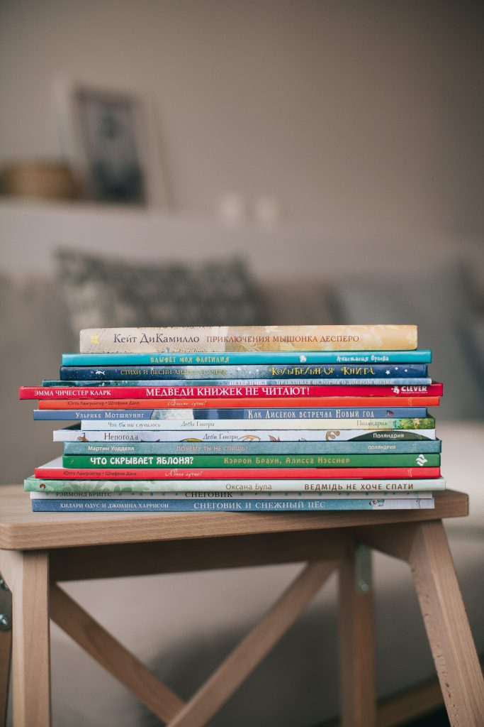 A stack of children's books sitting on a wooden table.