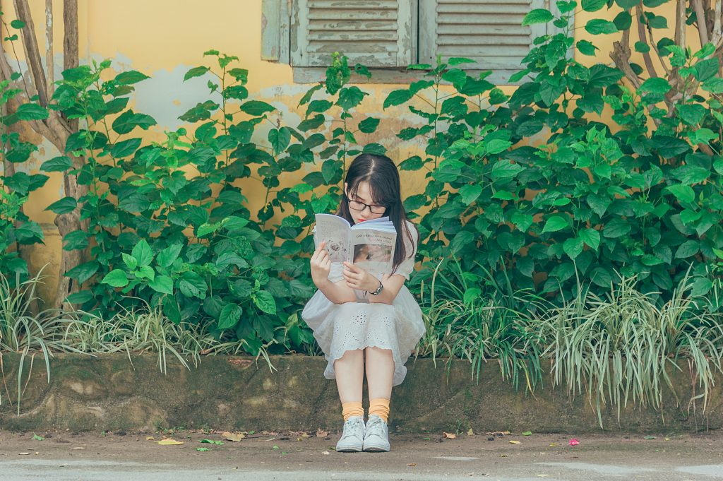 A young girl sitting on a garden wall completely absorbed in the books she is reading.
