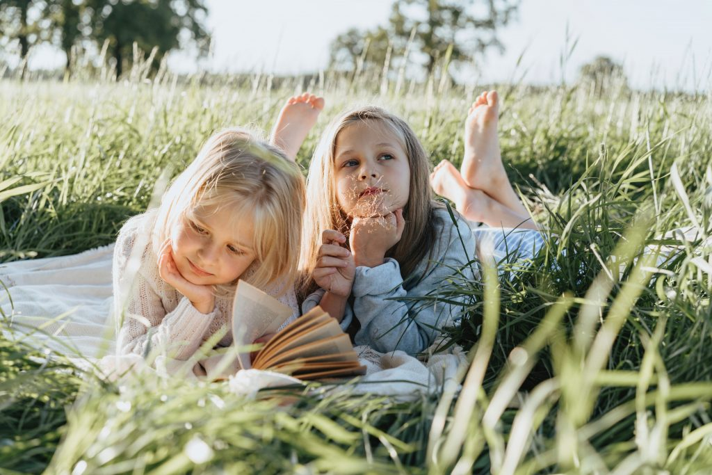 Two young girls laying on their stomachs in tall grass and reading their favorite books.