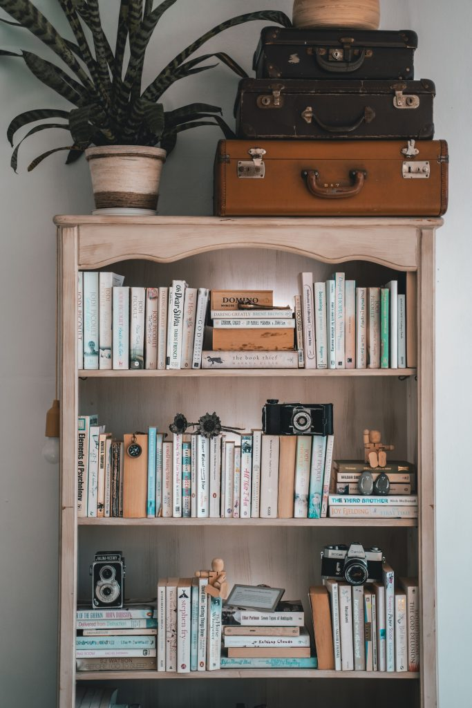 A wooden bookshelf laden with books, just waiting to be read.